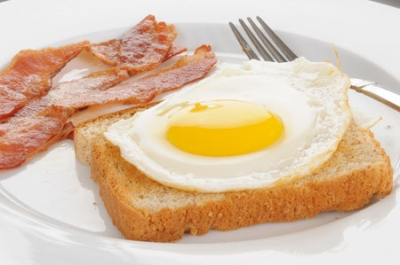 fired egg: A fired egg on a slice of toast with bacon Stock Photo