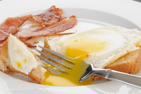 Close up of a fried egg on toast with bacon