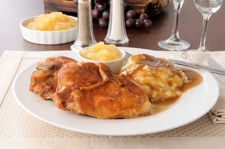 breaded pork chop: A breaded pork chop dinner with applesauce and mashed potatoes iwth muchroom gravy