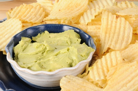 A plate of potato chips and guacamole dip