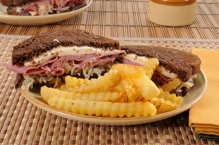 A grilled Reuben sandwich and fries photo