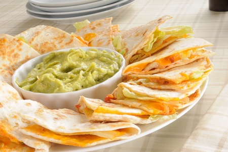 A plate of cheese quesadillas with guacamole photo