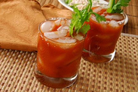 Bloody Mary cocktails or vegetable juice on a bamboo counter