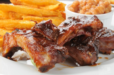 Close up of beef or pork ribs with fries and baked beans