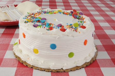 A white cake with candy sprinkles on top photo