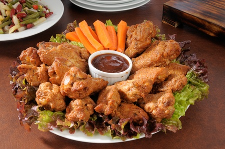 A party tray with chicken wings and carrot sticks photo