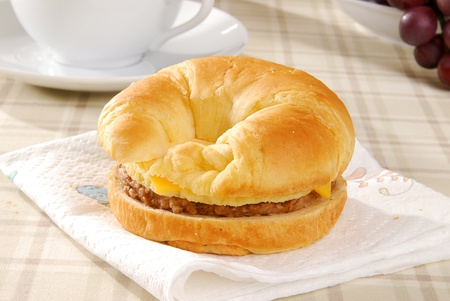 A sausage and egg croissant with coffee