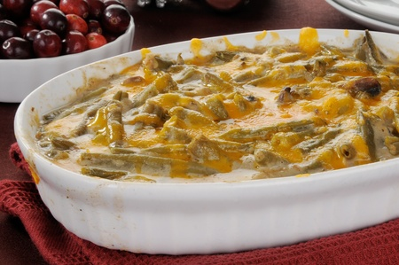 casserole dish: A green bean casserole with fresh cranberries in the background