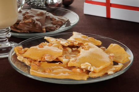 A plate of peanut brittle with chocolates, hot cocoa and Chrismas ornaments photo