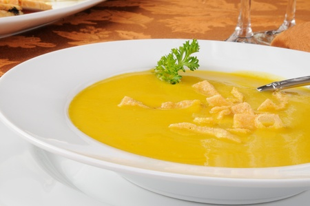 Close up of a bowl of butternut squash soup with fried garlic wonton strips Stock Photo