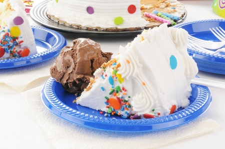 A slice of birthday cake and a scoop of chocolate ice cream