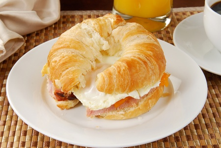 A ham and egg croissant with coffee and orange juice photo