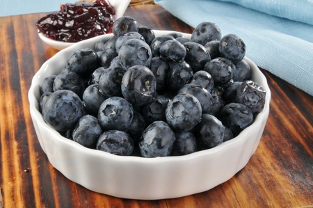 A bowl of fresh blueberries with a spoonful of jam Banco de Imagens