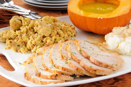 Turkey, dressing, mashed potatoes and pumpkin soup served family style for a holiday dinner Stock Photo - 12268579