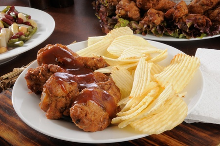 Party buffet with a plate of buffalo wings and potato chips in the foreground photo