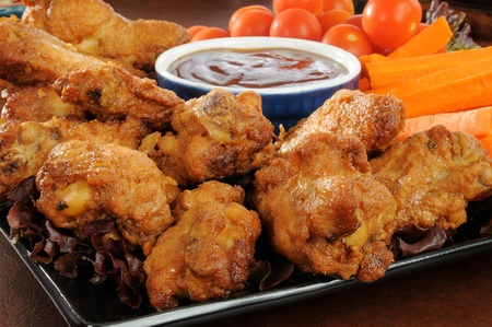 Closeup photo of a party tray with buffalo wings, carrot sticks and cherry tomates photo