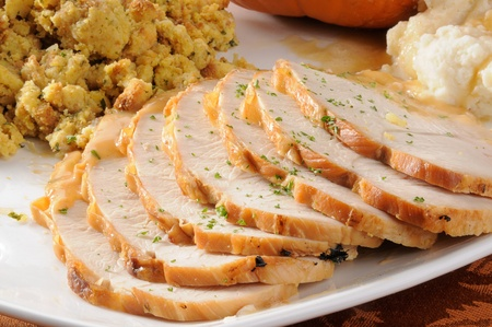 A serving platter with sliced turkey breast with mashed potatoes and stuffing Фото со стока
