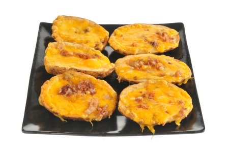 A plate of potato skins with cheese and bacon bits