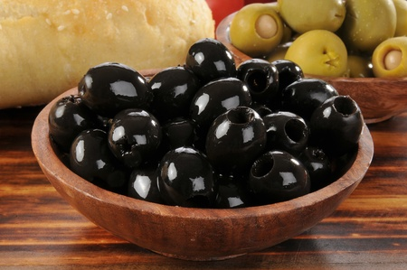 A wooden bowl of black olives with a loaf of bread in the background