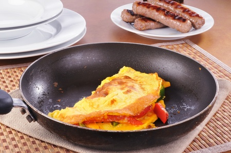 A skillet with a western omelet and a plate of sausage photo