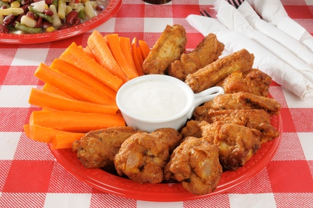 a plate of buffalo wings and carrots with a four bean salad photo