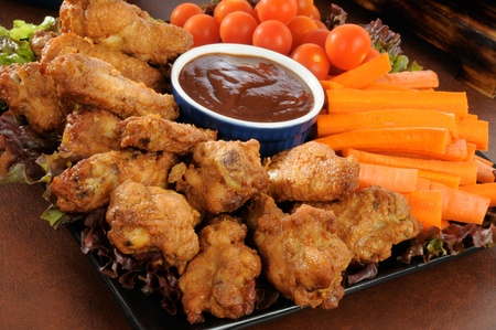 party tray: A snack tray with buffalo wings, carrot sticks and cherry tomatoes