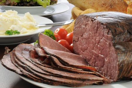 Thin sliced slow cooked roast beef with mashed potatoes and salad photo
