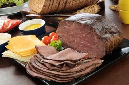 Sliced roast beef  with cheeses, breads and condiments photo