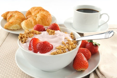 A breakfast of croissants, yogurt, strawberries and black coffee