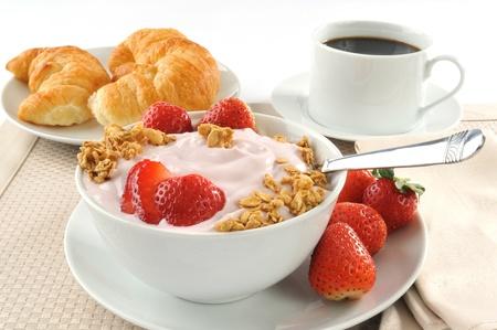 A breakfast of croissants, yogurt, strawberries and black coffee