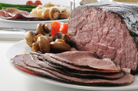 Thin sliced rare roast beef on the dinner table Фото со стока