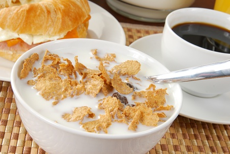 A bolw of corn flakes with raisins and a croissant sandwich photo