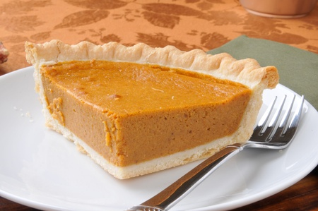 a slice of pumpkin pie on a plate with a fork photo