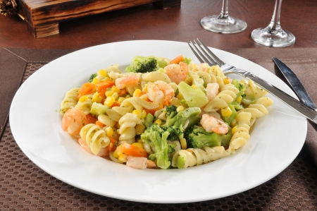 A bowl of garlic shrimp with pasta and vegetables