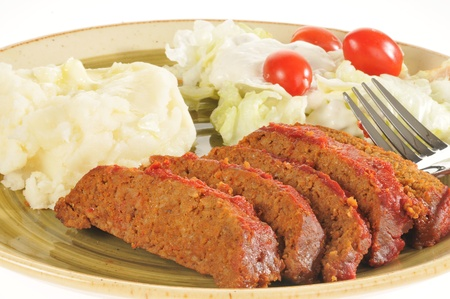 A closeup of a meatloaf dinner on a white background photo