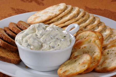 dipping: A plate of crackers, melba toast and spinich dip Stock Photo