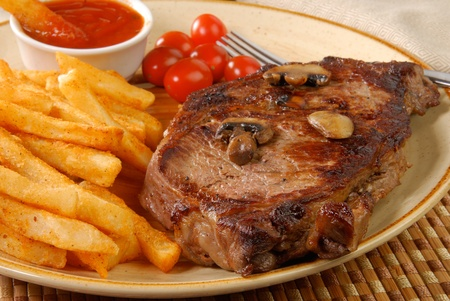 A grilled rib steak with french fries, closeup photo