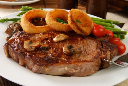 A grilled rib steak topped with onion rings Фото со стока