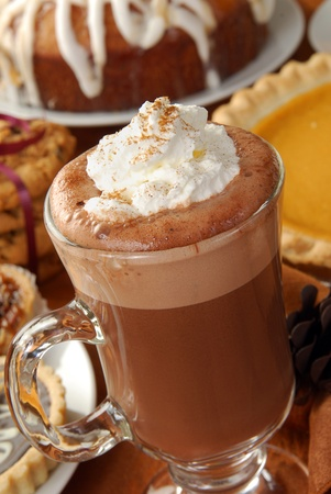 topped: A cappuccino topped with whipped cream and cinnamon on a dessert table
