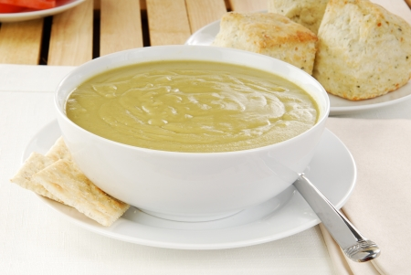 A bowl of split pea soup with saltine crackers