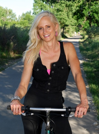 An attractive mature woman riding a bicycle Stock Photo