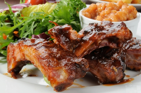 Macro photo of baby back ribs drenched in barbecue sauce with baked beans and greens