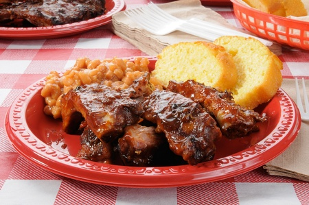 A plate of barbecued ribs and baked beans on a picnic table Stock Photo