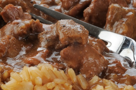 Closeup of a fork full of beef with gravy and brown rice