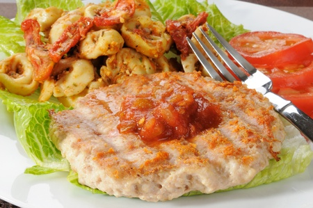 A grilled ground chicken or turkey patty with tortellini and roasted tomato pesto Stok Fotoğraf