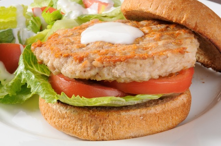 Closeup of a low fat healthy chicken or turkey burger with a salad Standard-Bild
