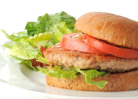 chicken sandwich: Una hamburguesa de pollo sana en un pan con ensalada