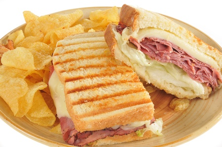 Close up photo of a roast beef and swiss cheese panini with potato chips photo