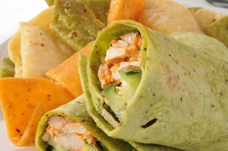Roasted chicken wrapped in vegetable tortilla shells with chips photo