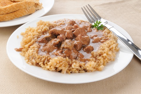 A plate of beef tips with brown rice and gravey